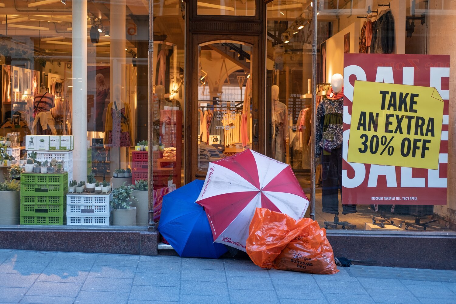 Consequences of the neoliberal agenda - a homeless person's camp in front a store going out of business.