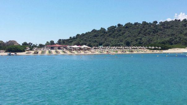 uitzicht van een azuurblauwe zee op een strand van een luxe verblijf