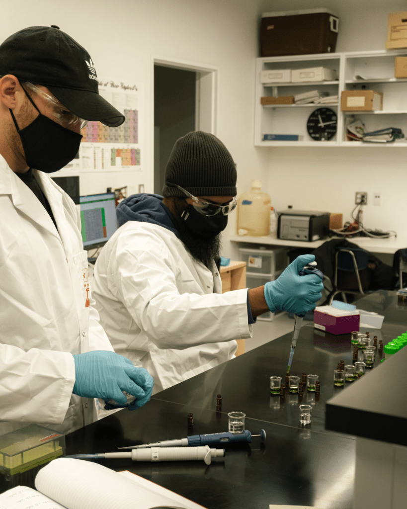 Two men extracting hop terpenes in a lab
