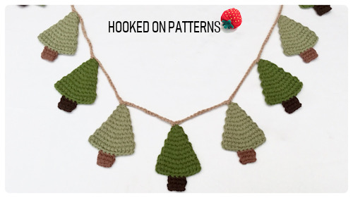 A crochet, rustic style, Christmas tree garland. Crafted in muted green and brown tones, hanging on a beige crocheted string. Image features the Hooked On Patterns logo.