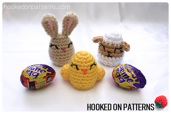A photo of a bunny, chick, and lamb crochet chocolate egg cover displayed with a couple of chocolate eggs.