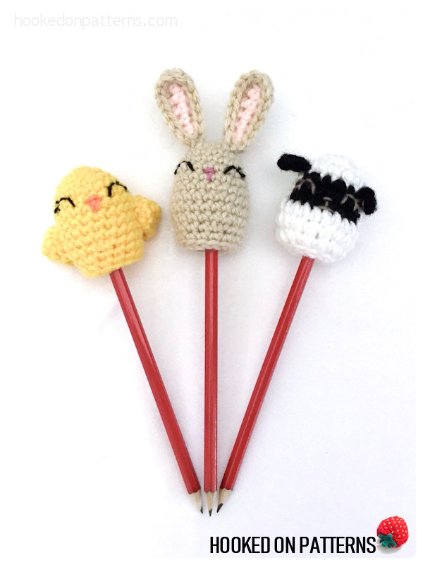 A photo showing the finished chick, bunny, and lamb egg shaped crochet pencil toppers on red pencils