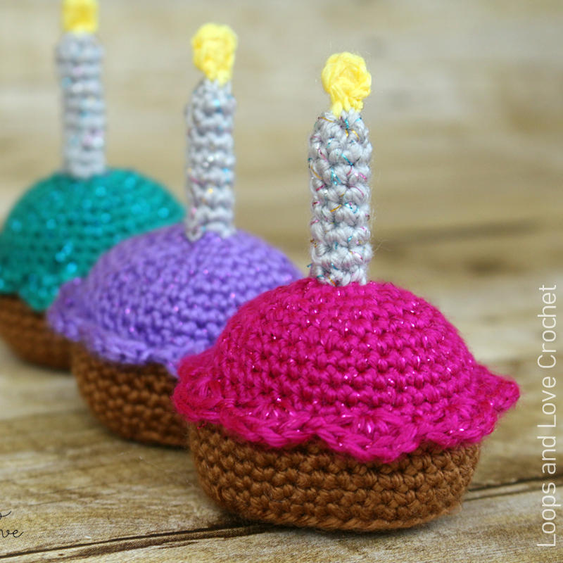 A photo of 3 crocheted cupcakes with candles on top.
