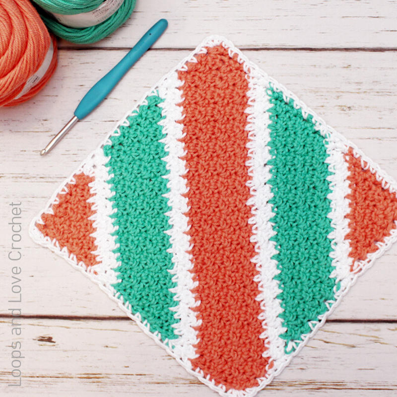 A photo of a textured crochet dishcloth with orange, green, and white diagonal stripes