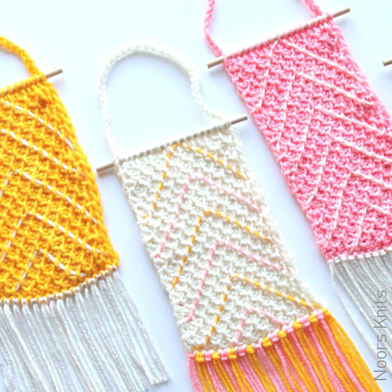 A photo of 3 textured wall hangings, crocheted in yellow, pink and white.