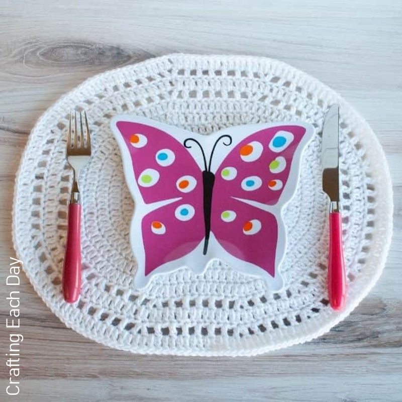 A photo of an oval shaped crocheted placemat, displayed under a butterfly shaped dish and pink cutlery.