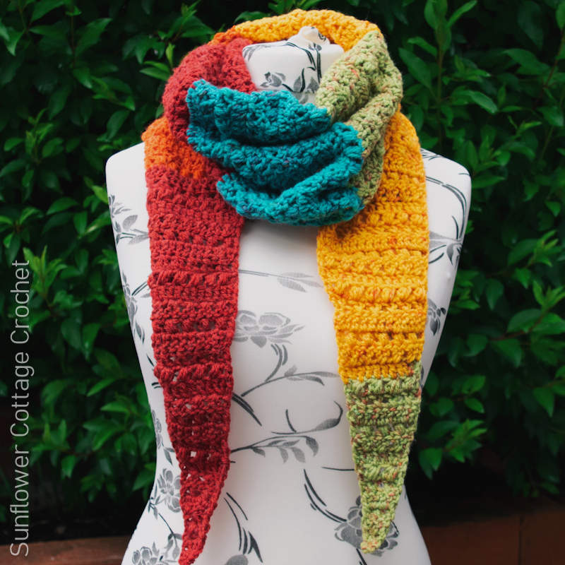 A photo of a colourful crochet scarf wrapped around a mannequin bust