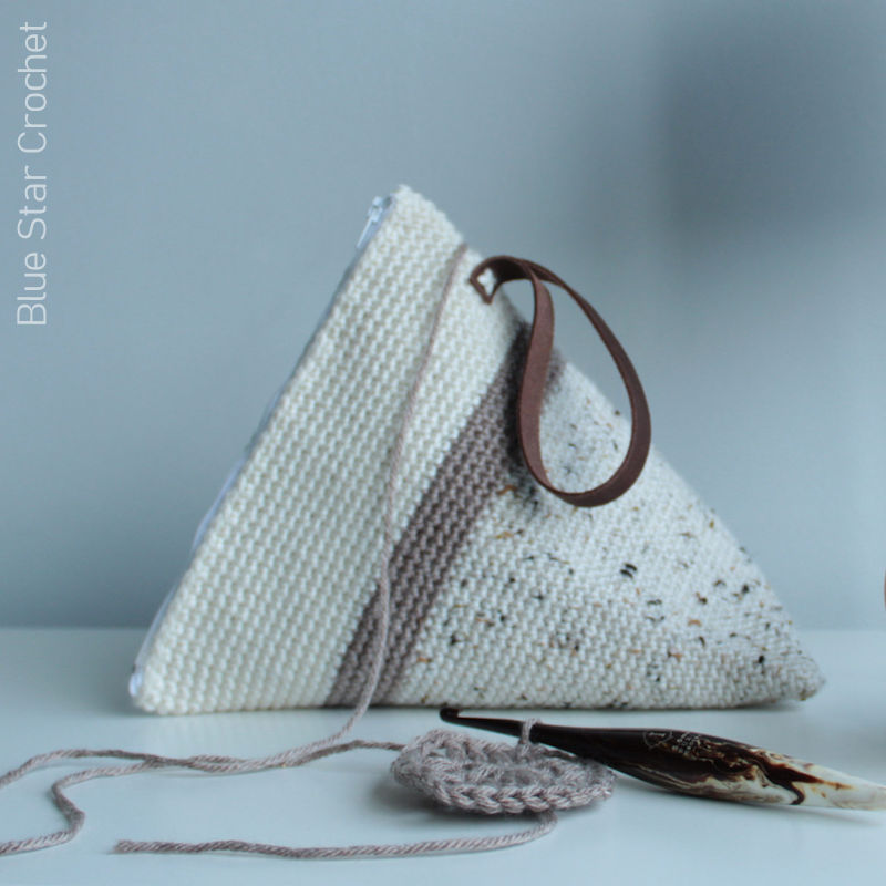 A photo of a crocheted yarn wedge shaped project bag with some crochet work and hook