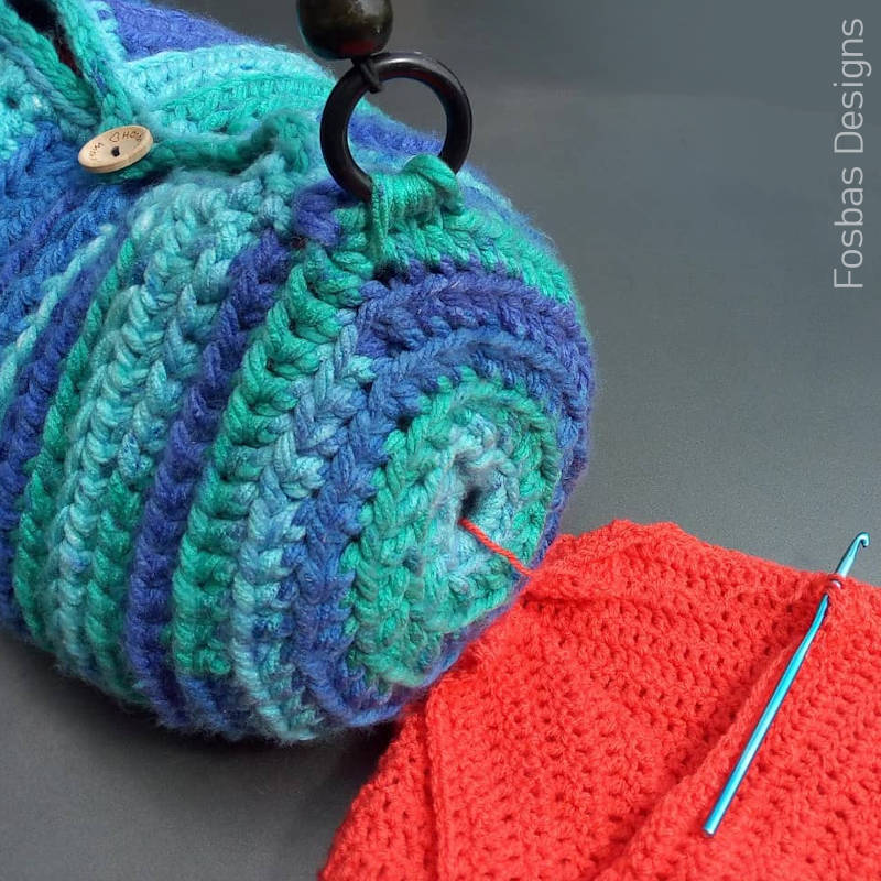 A close up photo of a crochet WIP bag with the working yarn coming through the side while crocheting
