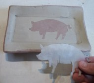 revealing the stenciled image on the greenware plate