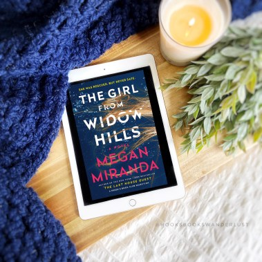 An iPad displays the ebook cover of The Girl From Widow Hills by Megan Miranda, laid on wood with a navy blue crochet blanket, candle, and greenery arranged around it.