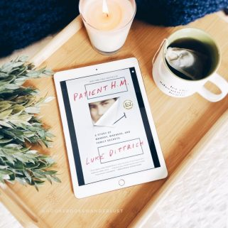 "An iPad showing the cover of the book ""Patient H.M."" by Luke Dittrich lays on a bamboo tray with greenery, a navy blue throw blanket, lit candle, and a cup of hot tea"