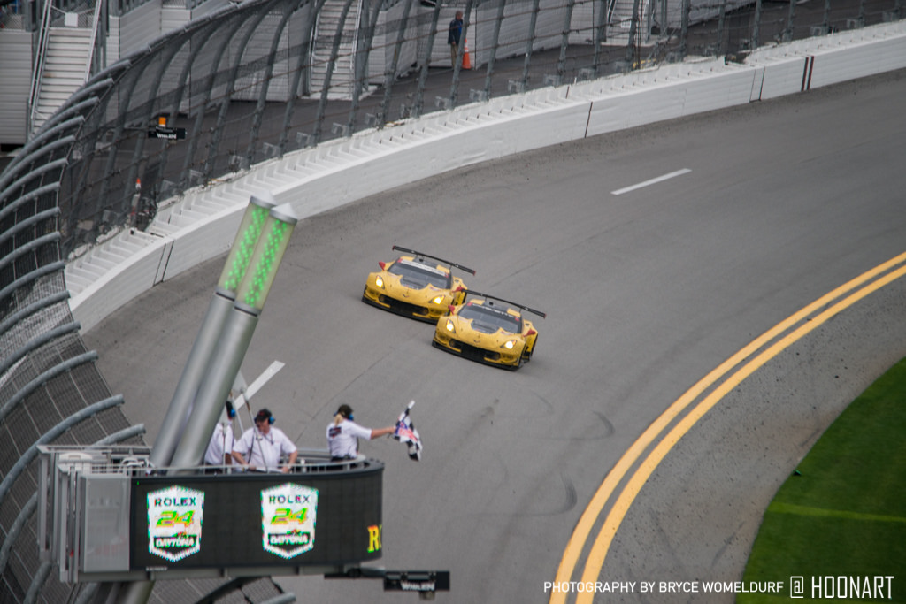 Two Corvette C7R's passing the finish line together.