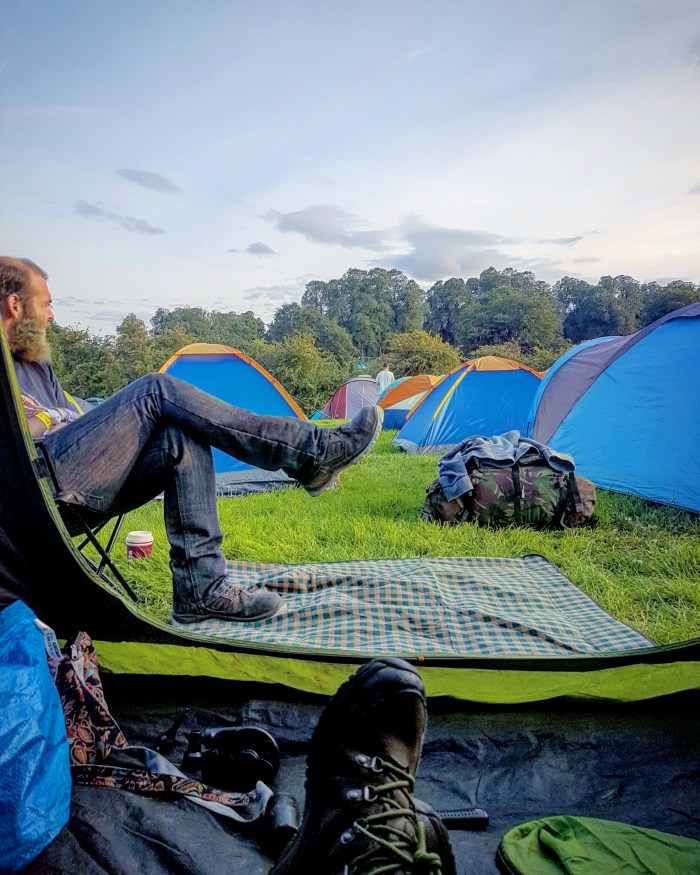 Henry sitting outside a tent at Leeds Festival - Travel Jobs - 5 Ways To See The World And Earn Money