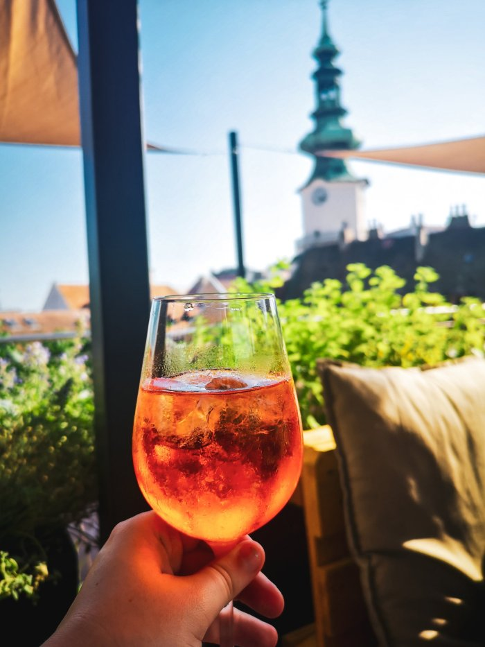 An Aperol Spritz in a hand with a view of the city-Bratislava-First-Timer's-Guide-Local-Guide-Hoopla-Adventures