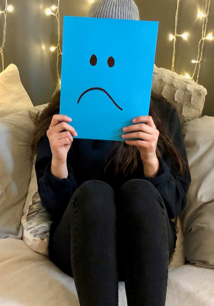 person covering their face with a blue piece of paper with a sad face on it