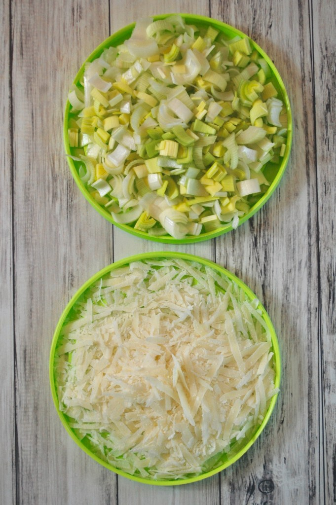 2 green plates topped with chopped leeks and grated parmesan cheese