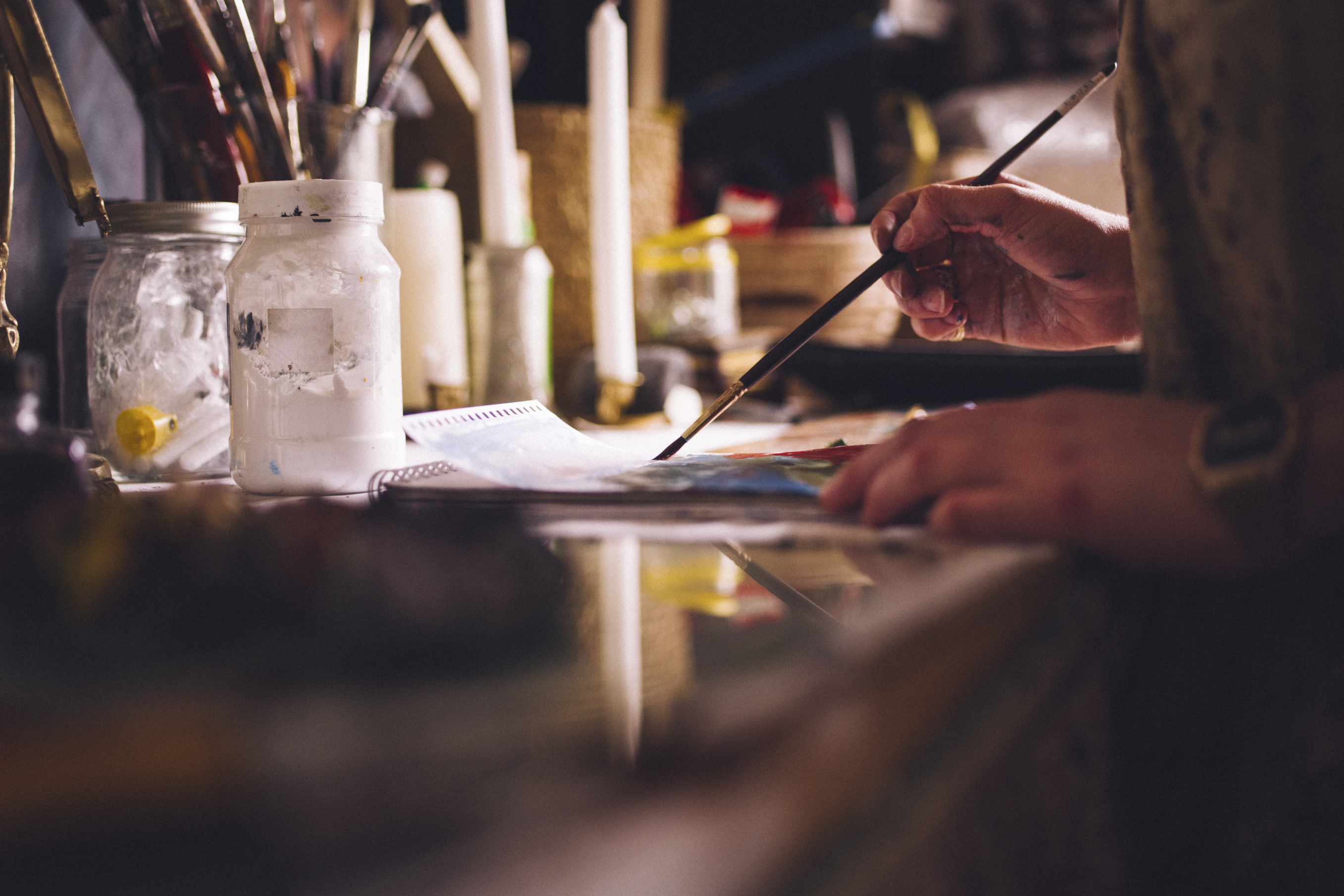 Cropped image of an artist's hands using a fine paintbrush while painting on paper at a desk with art and craft equipment all around