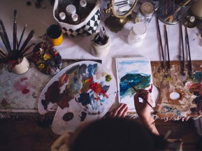 Top view of an artist painting with bright colors on a piece of paper on a high table with art and craft equipment and a palette