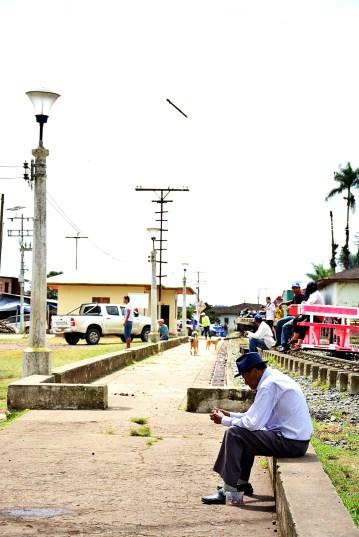 Un hombre de la tercera edad se pasea y come un babano en la plaza cerca a la vía ferrea.