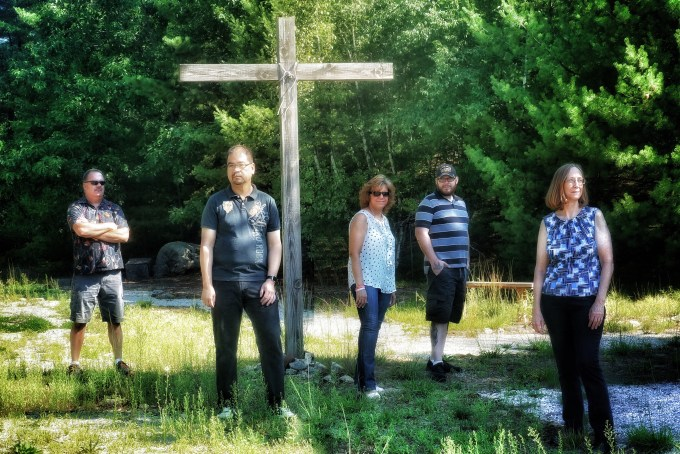 Members of Strong Tower standing around a cross