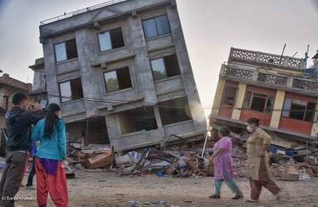 People watch in front of two collapsed houses