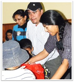 Impoverished families receiving bags and baskets full of foodstuffs, clothes and toys