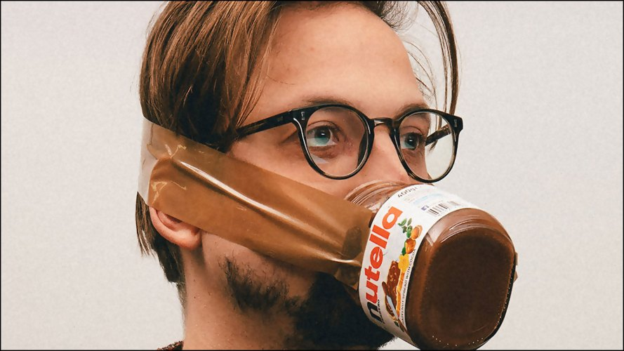 man wearing a jar of nutella as face mask