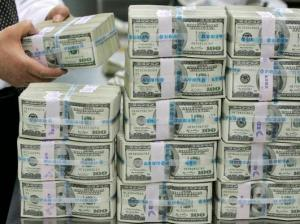 A bank employee counts one hundred dollar notes at a bank in Seoul