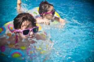 two children in the pool with sunglasses