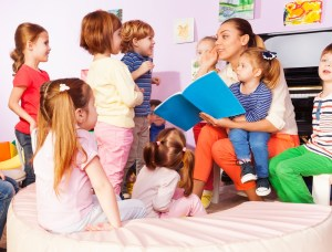a daycare provider reading and playing with kids