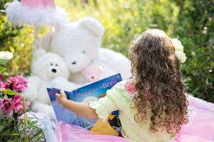 a little girl reading to her teddy bears