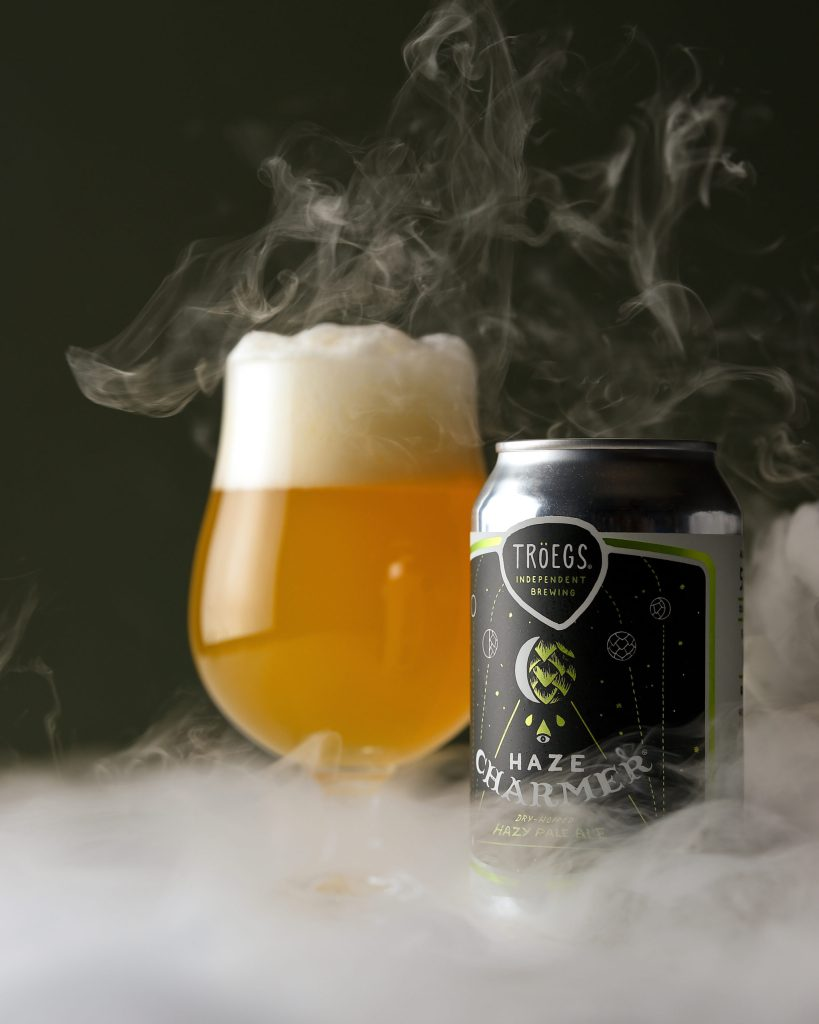 Haze Charmer can and poured glass of the hazy IPA, with mist in the foreground and background.