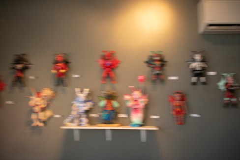 Blurry photo of winged creature dolls on the wall at Gigantic Brewing.