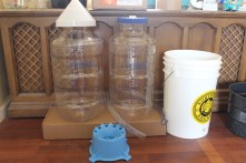 These are the carboys or fermentation chambers. The big one on the left is the 6.5 gallon primary fermentation chamber, and the smaller one on the right is the secondary fermenter. Also included in the shot is the white bottling bucket on the far right, the carboy stand for cleaning them on the bottom, a blowoff tube in between the carboys, and the carboys are on top the brewing tools box.