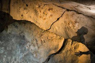 Huellas de manos, algunas infantiles, marcan las paredes de una cueva junto a la sombra de Dante García Serrano, ayudante de Guillermo de Anda. Esta cueva probablemente era parte de un paisaje ritual que incluía cuatro cenotes en los que los mayas dejaron más huellas de manos, huesos humanos y ofrendas de cerámica. paulnicklen.com