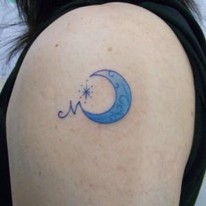 腕にコインサイズの月とイニシャルのタトゥー