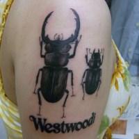 腕にくわがたと文字のタトゥー