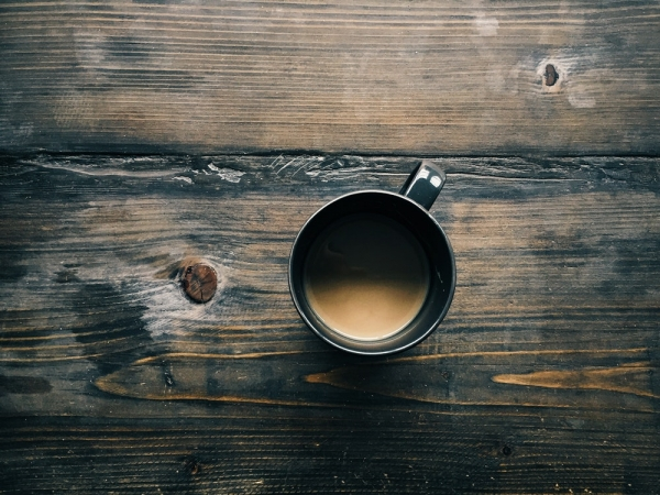 An overhead shot of a cup of coffee on a wooden surface