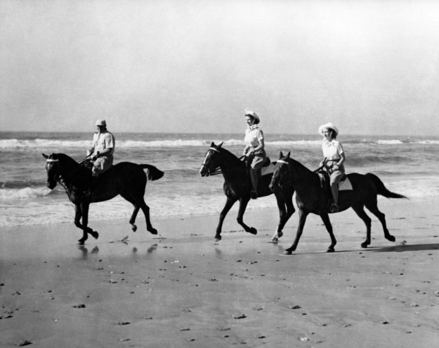 "The Princesses enjoyed an off-duty break from the royal tour of South Africa when they went riding on the golden sands of Bonza Beach, East London, Princess Elizabeth (centre) is riding Yvonne Hayhoe's 'Jill"" while Princess Margaret rides 'Treasure' owned by Pat O'Reilly of East London, who is seen escorting the Princesses."