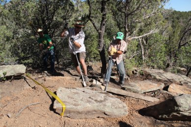 Griphoisting a stone into place above a drop from left to right--trail foremen Tyson Swasey, Gordon Rhodes and Dusty Bender.
