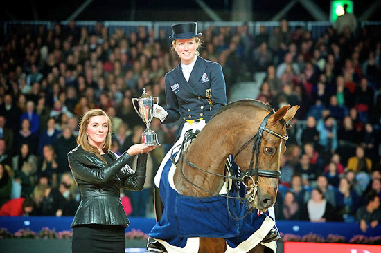 Germany's Helen Langehanenberg and Damon Hill NRW receiving the Reem Acra Trophy from Heather Schmidt of Reem Acra after victory in the sixth leg of the Reem Acra FEI World Cup Dressage Western European League series at Amsterdam, The Netherlands on Saturday.