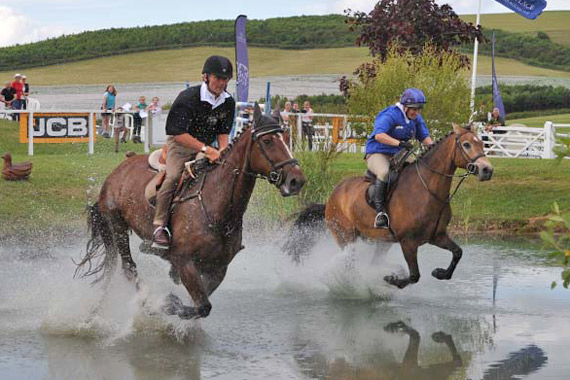 John Francome, nearest camera, and Zara Phillips battle it out in the JCB Champions Challenge.