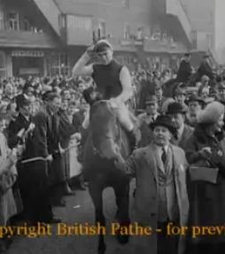 Michael Scudamore salutes the camera after winning the 1959 Grand National on Oxo.