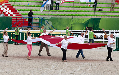 Equine Canada President Al Patterson, Bromont OC President Paul Coté, and Bromont Olympic Equestrian Park General Manager Roger Deslauriers, along with their wives, proudly parade the Canadian flag around the d'Ornano Stadium during the handover ceremony at the Alltech FEI World Equestrian Games 2014.