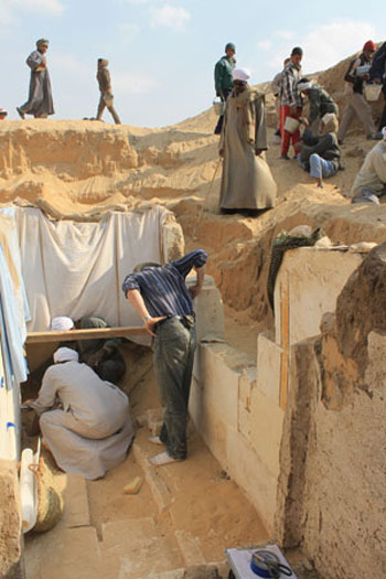 Team members work to excavate the burial chamber of Woseribre Senebkay, with sheets covering a painted wall decoration. Photo: Josef Wegner, Penn Museum