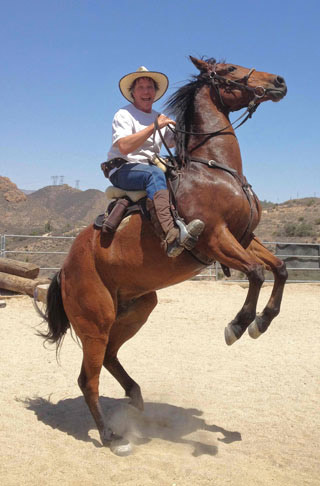 """Colin Dangaard pictured on his horse, Ringo. """"Somebody gave him to me because he reared. So I decided to not only let him do that but encourage him. He now rears beautifully on demand , can even walk backwards. It is nothing I taught him. He just loves doing it."""" Ringo was recently sold to a Hollywood horse handler."""