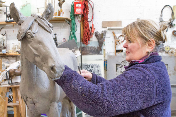 Judy Boyt crafting the clay maquette of World Horse Welfare May.