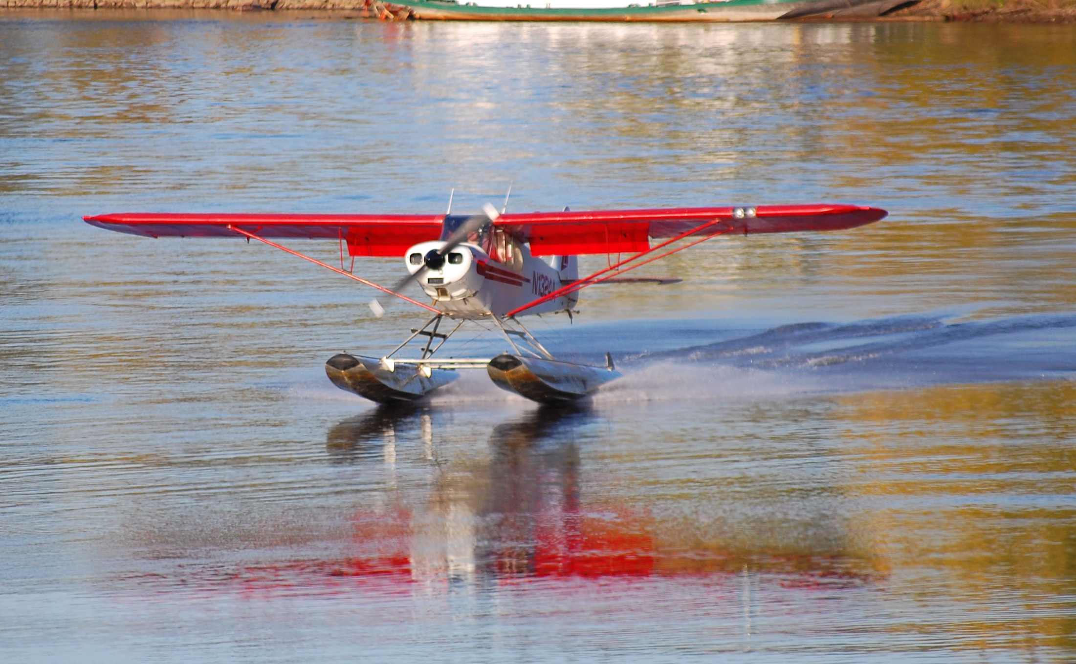 A Piper Cub on floats taking off from the river.