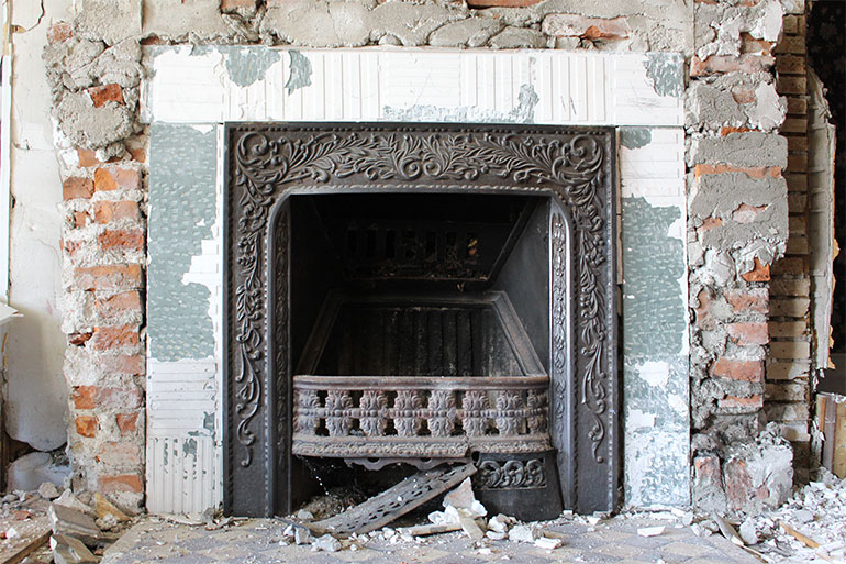 Work ongoing: The face, mantle, and grill of one of the downstairs fireplaces will be reused in another project.